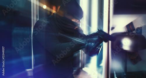 Valokuva Einbrecher mit Pistole und Taschenlampe