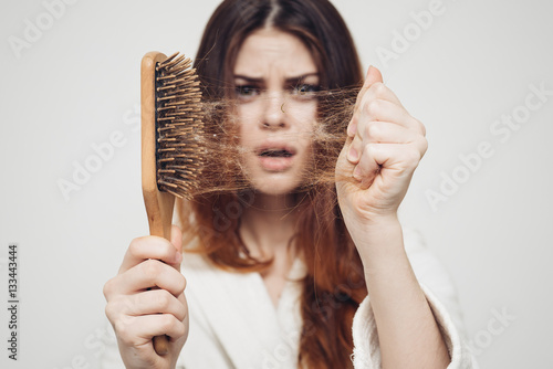 Fotografia  girl with a comb in his hand on a white background distressed hair