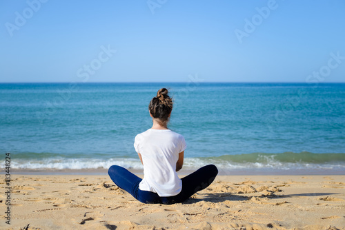 Foto op Aluminium Ontspanning Back view of woman doing exercises on sandy beach sunny background outdoors