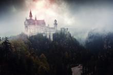 Neuschwanstein Castle In Germany, Bavaria. Artistic Post-production Stylized As Ominous Palace Of Dark Forces, Ominous Clouds And Mist At Background And Red Glowing Light Over Pinnacle Castle Tower.