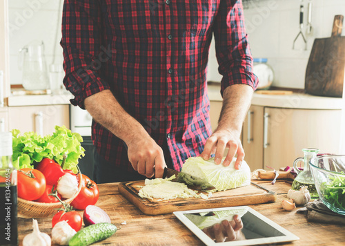 Foto op Canvas Koken Man cooking healthy meal in the home kitchen