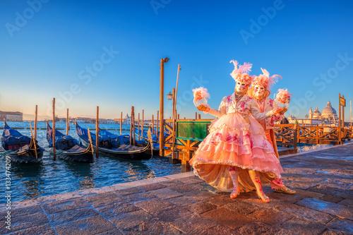 Famous carnival masks against gondolas in Venice, Italy