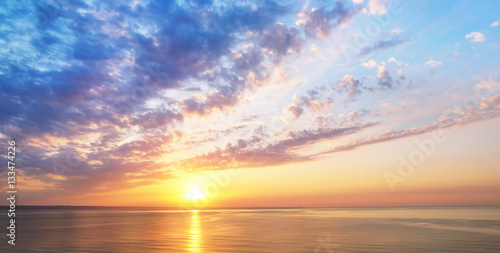 Foto op Plexiglas Landschappen Panorama view of sunset sunrise sea ocean summer with textured clouds and beautiful sunlight in blue gold tones. Romantic tender wallpaper, soft air harmonious stunning artistic image.