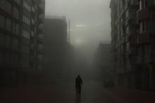 Cyclist On A Street In Foggy City