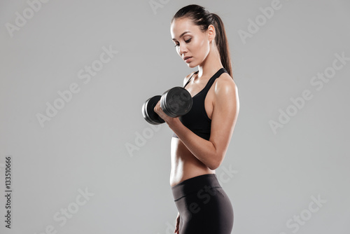 Fotografia  Side view of Young Sporting woman using dumbbell