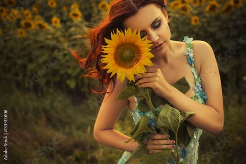 Beautiful brunette caucasian woman in blue dress at the park in flowers on a  summer sunset holding sunflowers 2e6c9636b