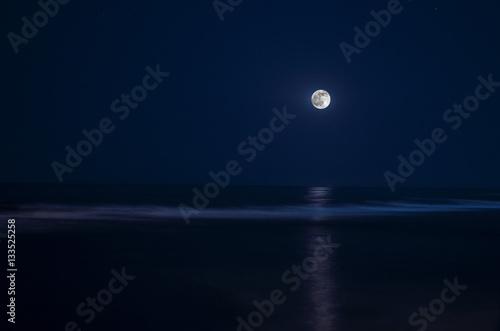 Full moon in night sky over moonlit water Fototapeta