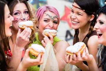 Frauen an Fastnacht essen zusammen Kreppel oder Pfannkuchen