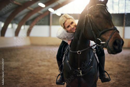 Smiling blonde female leaning on black horseback Tablou Canvas