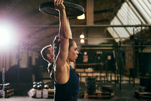 Obraz Two young sportive athletes exercising with weights - fototapety do salonu