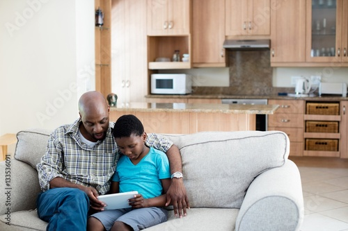 Father and son using digital tablet in living room