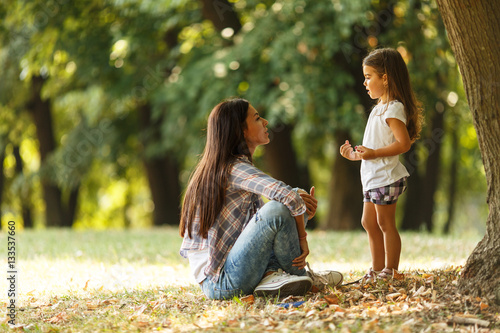 Fotografiet  Mother holding her daughter and playing around the park on beautiful morning