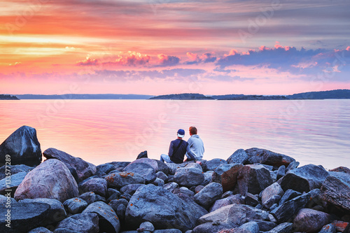Wall Murals Light pink Male couple sitting on stones at sea shore looking at amazing sunset scene background with dramatic sky, rear view. Picturesque landscape of Sweden sea coastline. Instagram toning.