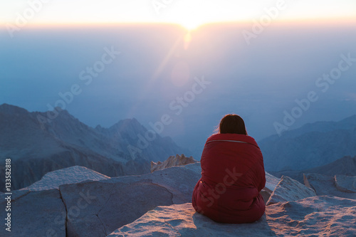 A young woman watches the sunrise from the top of a mountain Plakat