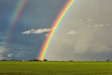Big Double Rainbow Over Green Field And Red Barn