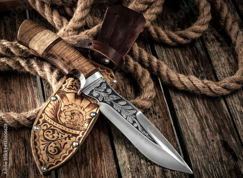 Poster Chasse Hunting Knife with leather sheath on a wooden table.