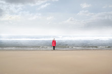 Single Woman In Red Raincoat Standing On A Beach Looking At The Stormy Sea
