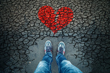 Lonely Man Standing On Cracked Asphalt Floor With Illustrated Cracked Broken Heart Symbol. Point Of View Perspective Used.