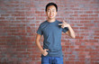 Asian man in blank grey t-shirt standing against brick wall