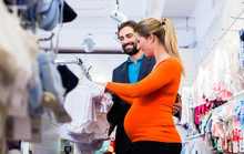 Pregnant Woman And Man Buying Baby Clothes In Store
