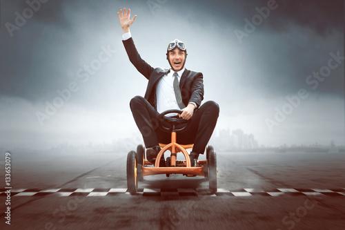Photographie Joyeux homme d'affaires sur la voiture à pédales