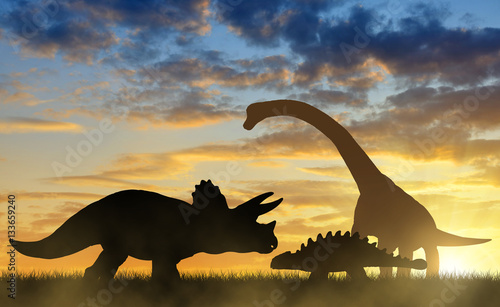 Silhouette of dinosaurs in the sunset.