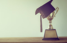 Graduation Cap With Champion Golden Trophy On Wood Table With Co
