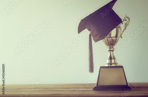 Cuadros en Lienzo graduation cap with champion golden trophy on wood table with co