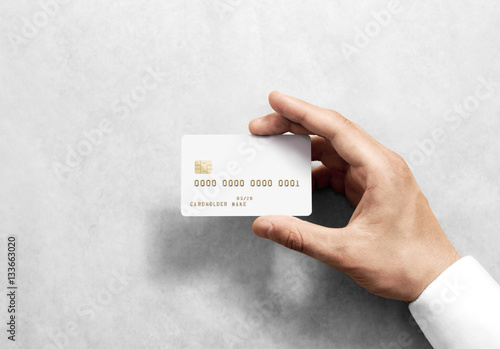 Fotografering  Hand holding blank white credit card mockup with chip and embossed gold info