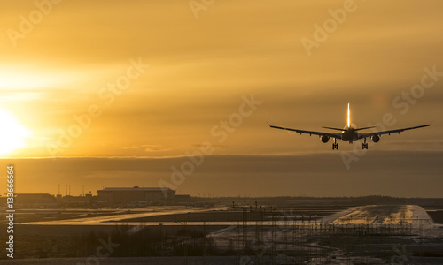 Photo  Commercial airliner landing to airport runway at sunset