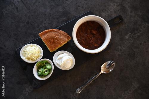 Chilli con carne, cornbread and accompaniments, overhead view Poster