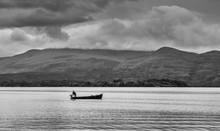 Man Fishing On Lake In Fishing...