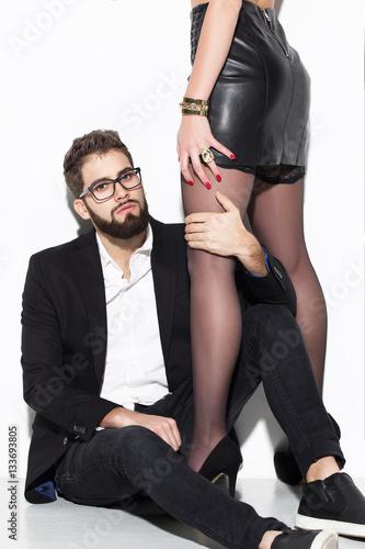 Plakat Młody stylowy hipster człowiek gospodarstwa bogata kobieta przez nogi