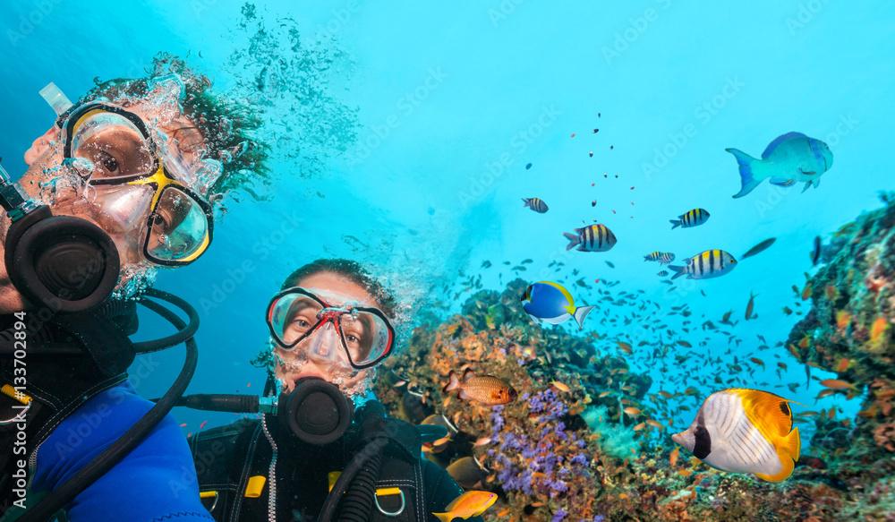 Fototapeta Scuba divers looking at camera underwater