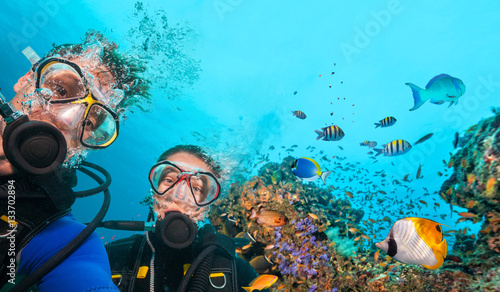 Spoed Fotobehang Duiken Scuba divers looking at camera underwater