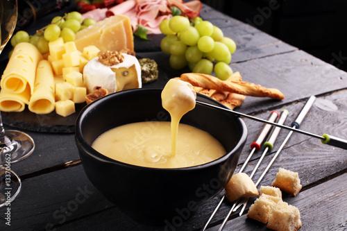 Fototapeta Wyśmienita szwajcarska kolacja fondue w zimowy wieczór z bukietem serów na desce obok podgrzewanego garnka z serowym fondue z dwoma widłami zanurzającymi chleb i białe wino w tawernie lub restauracji