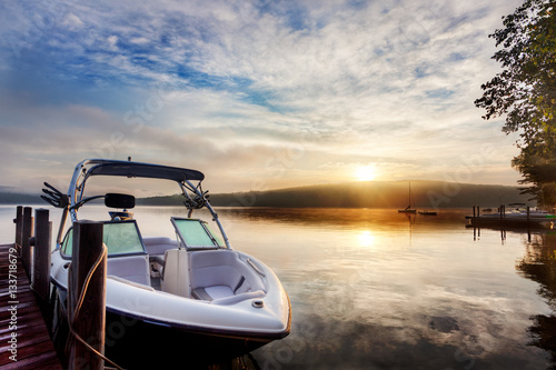 Fotografia Sun and mist on boat dock at sunrise on a summer day