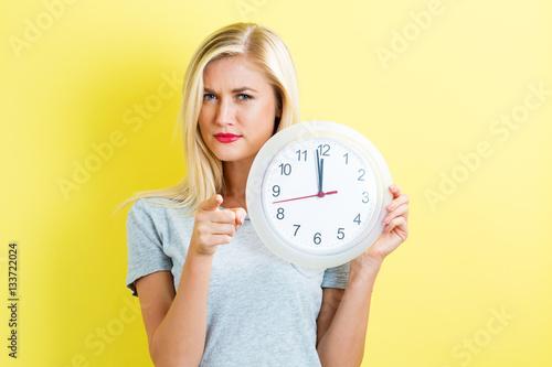 Fényképezés  Woman holding clock showing nearly 12