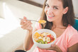 attractive young woman enjoying fruit salad