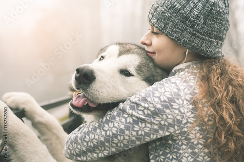 Photo  Image of young girl with her dog, alaskan malamute, outdoor