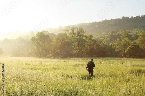 Fotografía  A man is hiking on grass field background early morning, sunny and blue sky