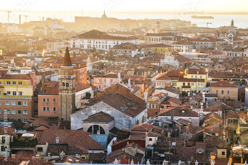 Foto op Canvas Europa Aerial view of Venice, Italy, at sunset with rooftops of buildings and warm sunlight.