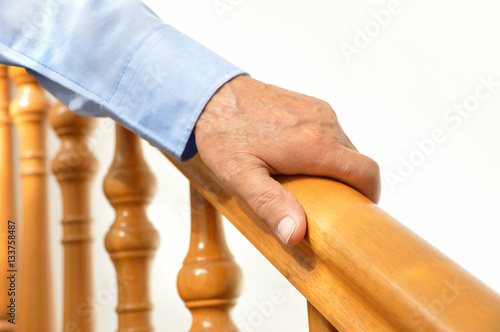 Fotobehang Trappen hand of senior man over a wooden railing