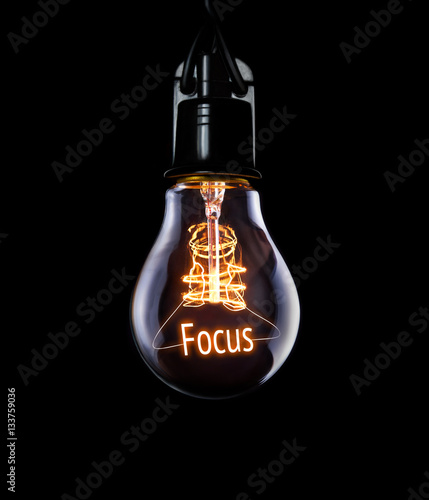 Photo  Hanging lightbulb with glowing Focus concept.