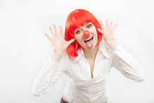 Pretty Young Brunette Caucasian Woman With Red Nose And Wig Making A Face On White Background