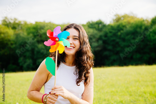 Fotografie, Obraz  Funny young woman holding a windmill