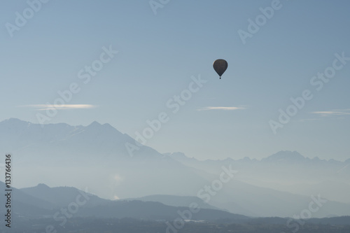 Foto op Canvas Luchtsport Hot air balloon flying over mountains landscape with winter haze