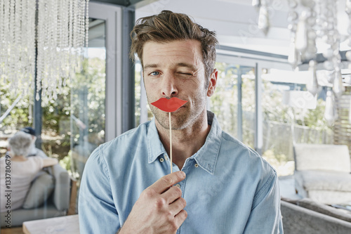 Man holding paper lips in front of his mouth