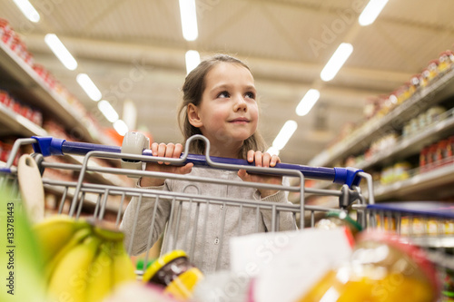 girl with food in shopping cart at grocery store Fototapete