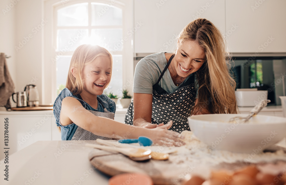 Fototapety, obrazy: Happy young girl with her mother making dough